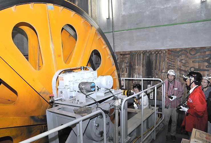千畳敷駅の機械室で巨大な滑車を見学する参加者たち