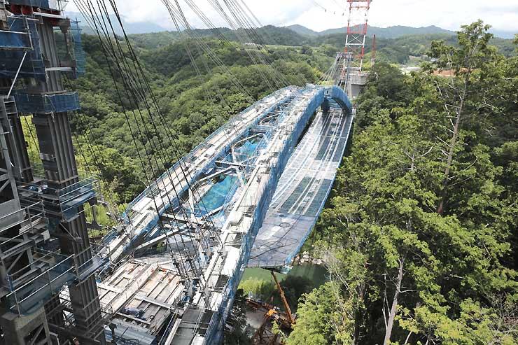 飯田市の名勝天竜峡で建設中の三遠南信道「天龍峡大橋」(仮称)。天竜川両岸をつなぐアーチ部分がほぼつながり、橋の形が見えてきた=14日