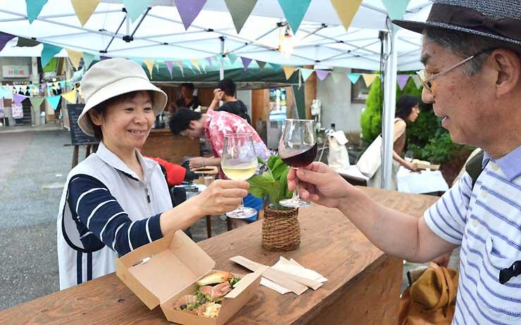 久石譲さんらが語る催しを開いた映画館前で、県産ワインや料理を楽しむ人たち=12日、長野市権堂町