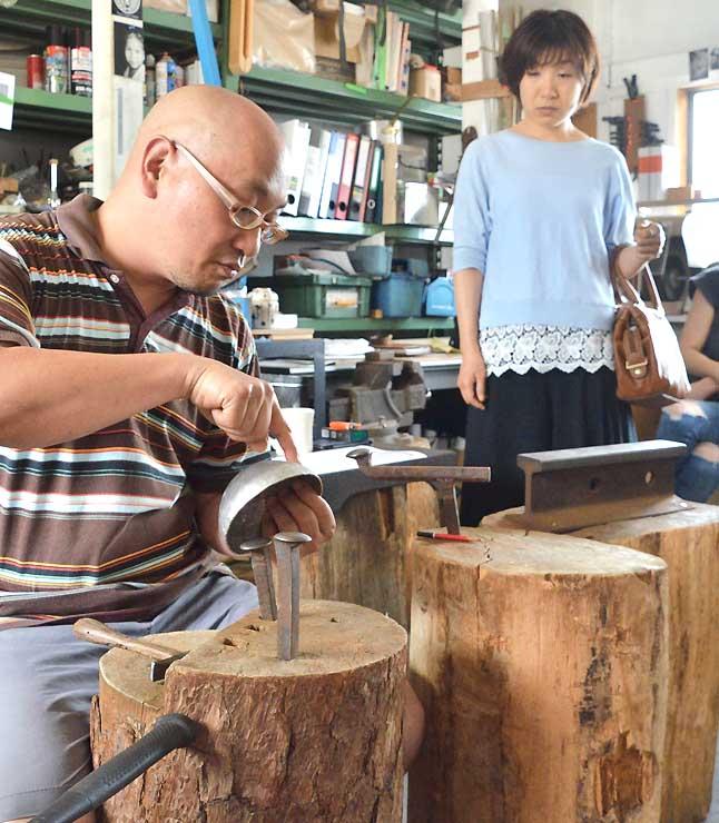 工房で見学者(右)に作品の作り方を解説する金属造形作家の角居さん=9日、長野市田町
