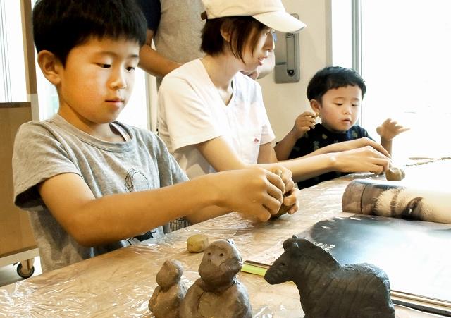 動物図鑑などを見ながら好みの作品を仕上げる参加者=15日、サンドーム福井の福井ものづくりキャンパス