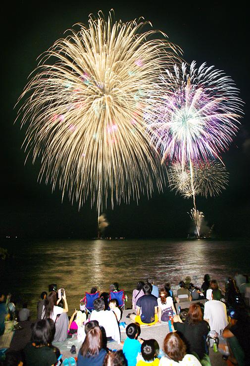 富山湾の夜空を鮮やかに染めた正三尺玉(左)やスターマイン(多重露光)=滑川市の和田の浜
