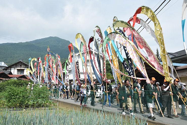 夫神岳(後方)から下山し、色鮮やかな幟を掲げて温泉街を目指す行列