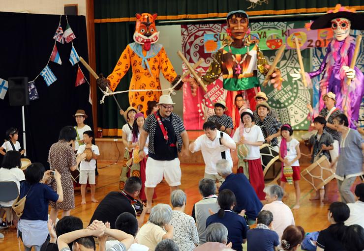 巨大人形隊のダンスとトゥーマラッカの演奏を楽しむ観衆=花椿