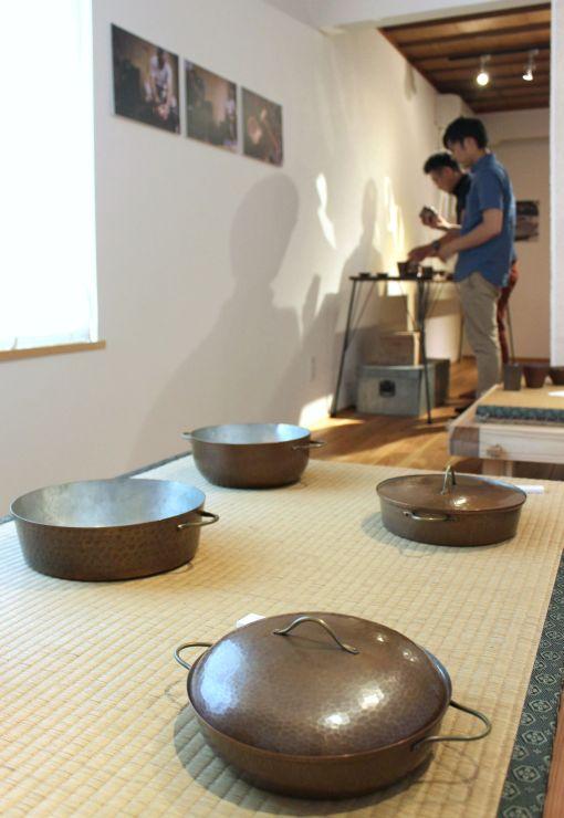 湯沸かしや鍋などの鎚起銅器の作品が並んだ展示会=18日、新潟市秋葉区新津本町3