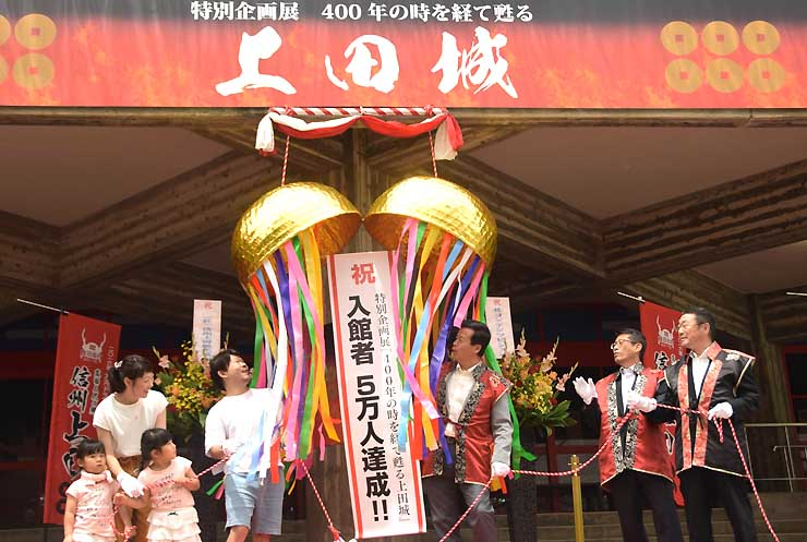 入館者5万人達成を祝い、くす玉を割る杉浦さん一家(左の4人)ら