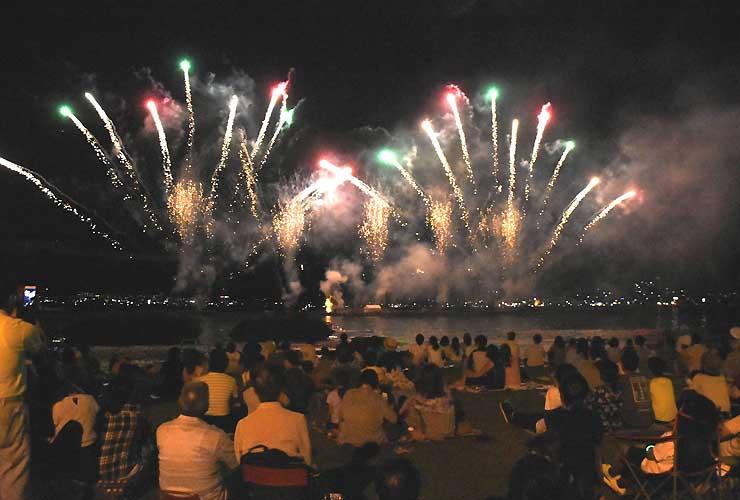 諏訪湖上で打ち上げた花火を見物する観客ら=17日午後8時