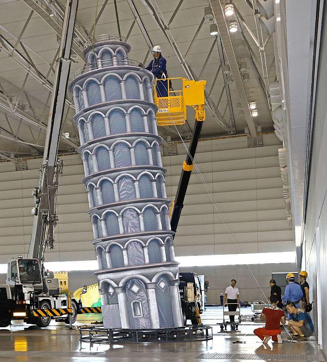 イタリアの「ピサの斜塔」など有名建造物を模した巨大なランタンの設置作業=19日、朱鷺メッセ