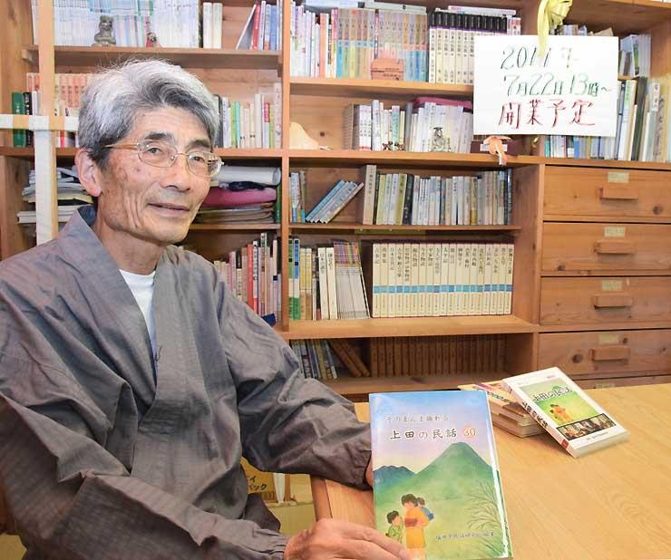 「民話カフェまほろば」としてオープンする部屋で、民話の本を手にする斎藤さん