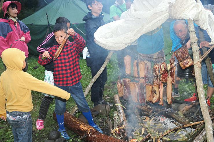 落ち葉や枯れ木を集めて火をたき、ベーコン作りに挑戦した参加者