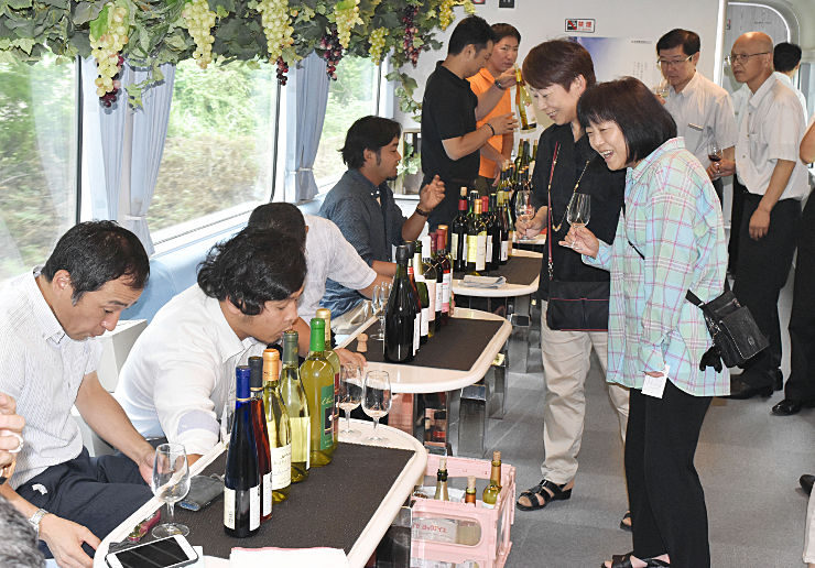 各蒸留所が提供するワインを試飲する乗客ら。車内にはブドウの飾り付けも