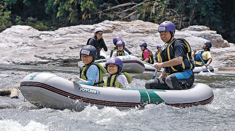 水しぶきを浴びながらボートで急流を下る子ども=白山市の手取峡谷