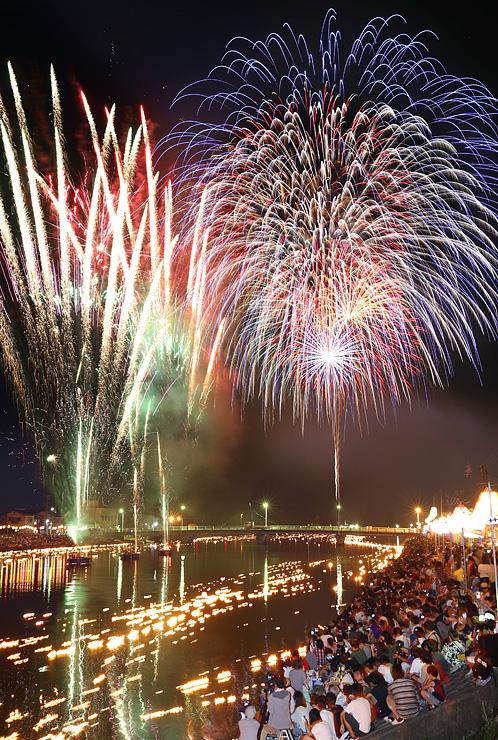 夜空を彩る大輪の花火と川面に漂う流し火(多重露光)=富山市水橋の白岩川河口付近