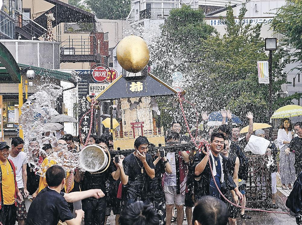 水を浴びながら神輿を担ぐ参加者=金沢市片町1丁目