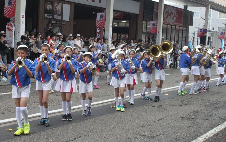 元気よく演奏するマーチングバンドの子どもたち=24日、上越市本町4のイレブンプラザ前