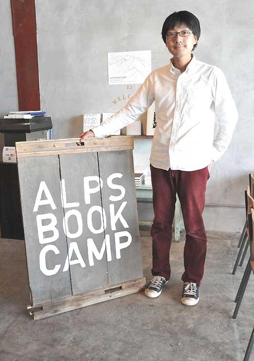 「アルプスブックキャンプ」の看板を示す菊地さん