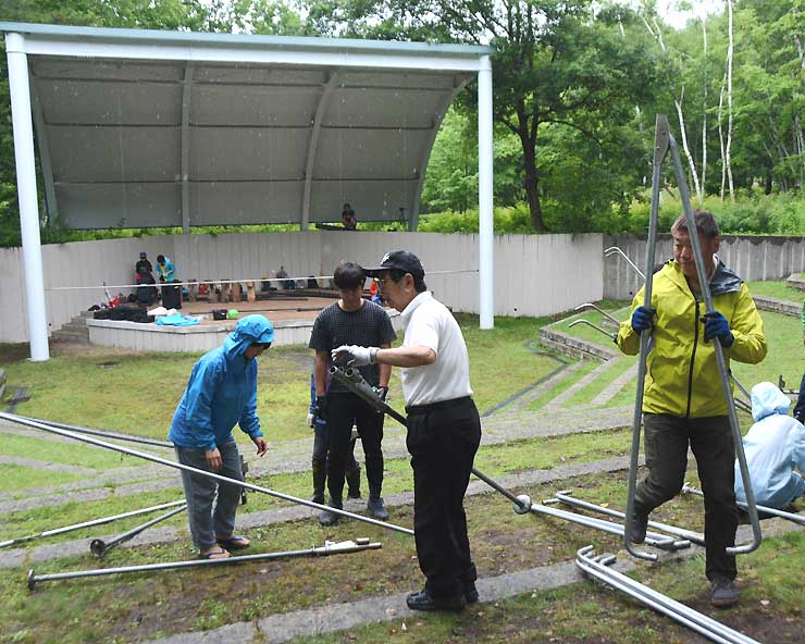 雨の中、映画祭の大型スクリーンやテントを設営する実行委員たち