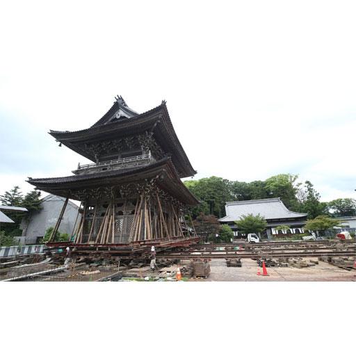「曳家」でレールの上を右から左へゆっくりと進む山門=輪島市門前町の總持寺祖院