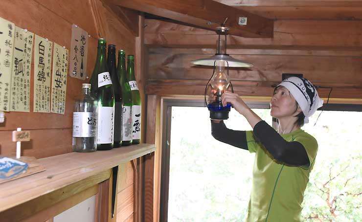 ランプに火をともす斎藤さん。棚には大好きな地酒を並べ、手書きで特徴を紹介している=27日