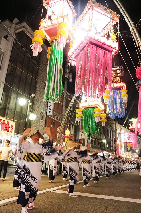 七夕飾りの下で踊りを披露する民踊街流しの参加者=南砺市福光