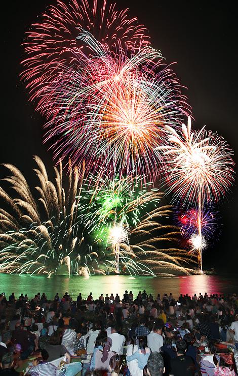 海上を鮮やかに彩った水中スターマインや大輪の打ち上げ花火=黒部市の生地浜(多重露光)