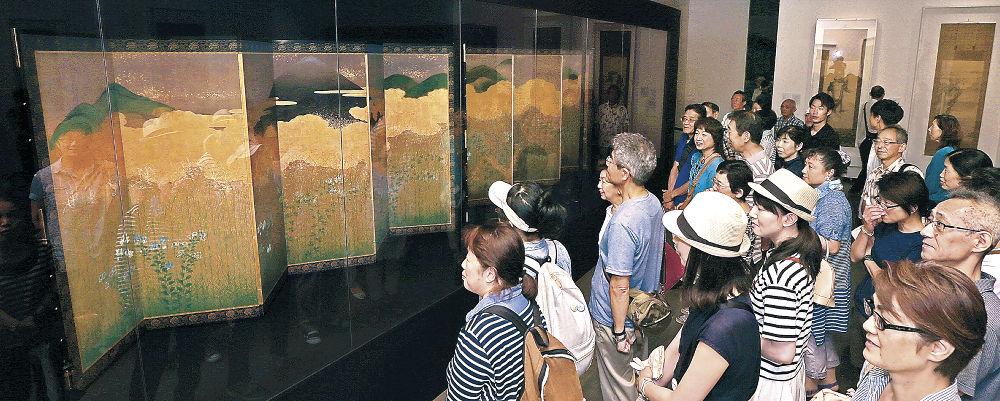 「武蔵野図屏風」にも見られる江戸期の洗練されたデザイン感覚に目を凝らす鑑賞者=金沢21世紀美術館