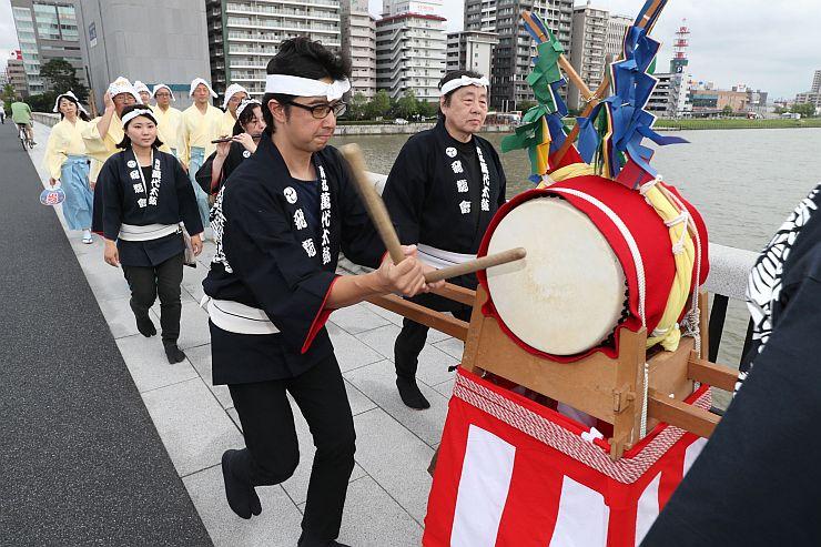萬代橋を練り歩くふれ太鼓の一行=28日、新潟市中央区