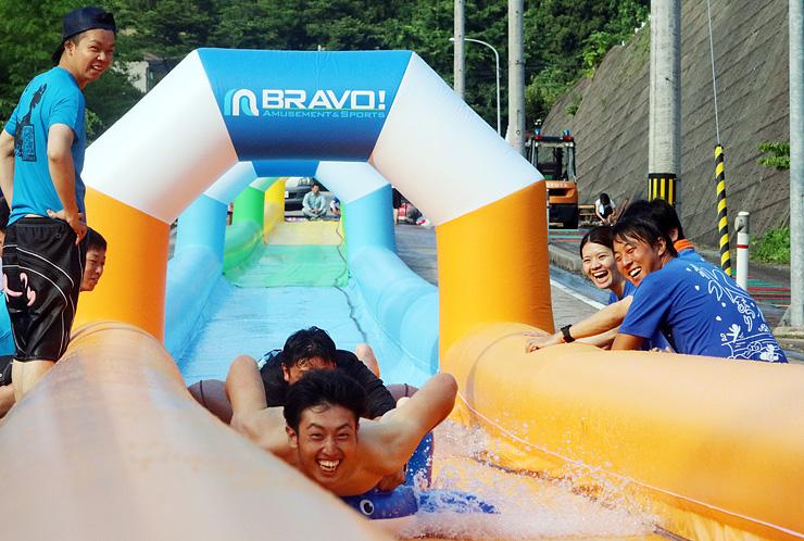 長さ100メートルのスライダーを滑り降りる参加者=庄川水記念公園近く