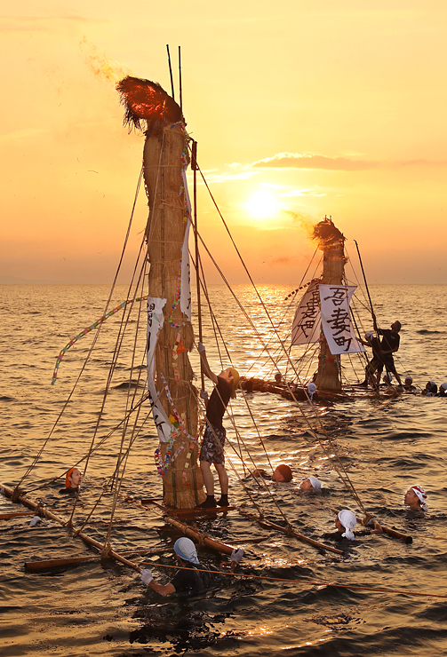 夕日に染まる海上で燃えるネブタ=滑川市中川原海岸(写真部部長デスク・垣地信治)