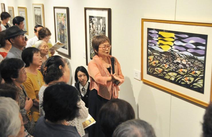 来館者に切り絵作品に込めた思いなどを説明する柳沢さん(中央)