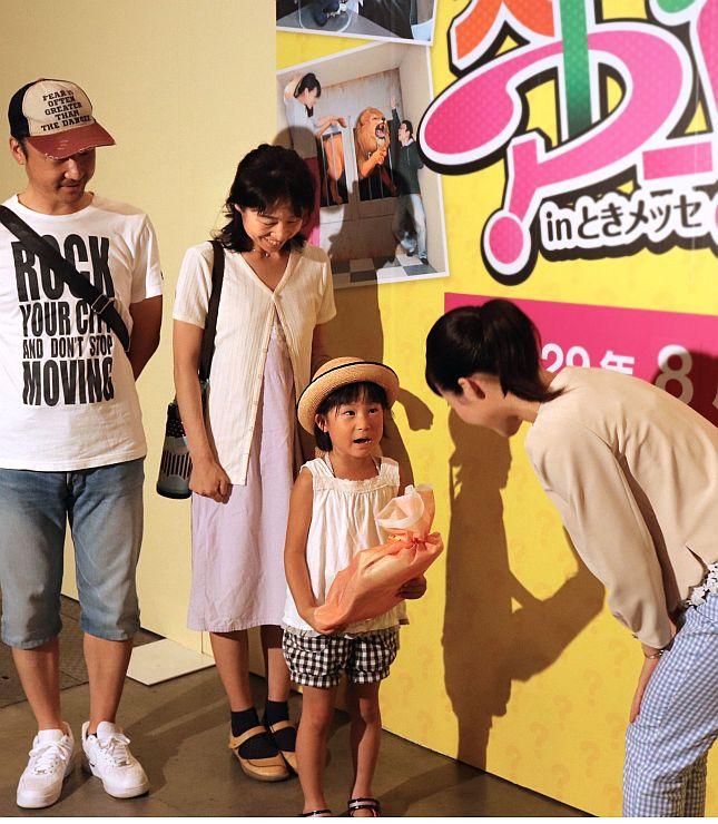 来場1万人目の記念品を受け取る女の子(中央)=4日、新潟市中央区