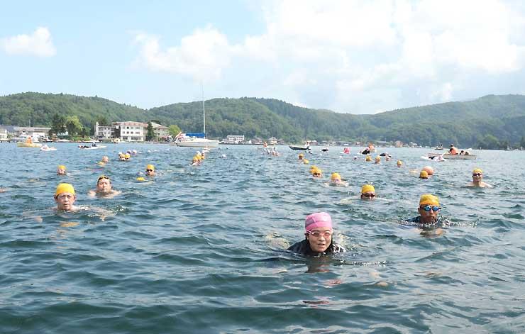 澄んだ湖面を隊列を組んで泳ぐ参加者たち