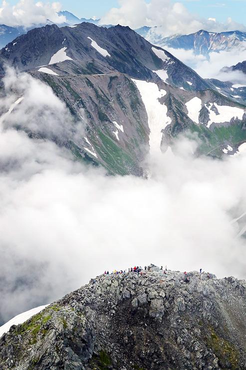 雲から突き出た剱岳山頂(手前)。大勢の登山者の姿が見られた。奥は立山三山=6日午前7時半ごろ