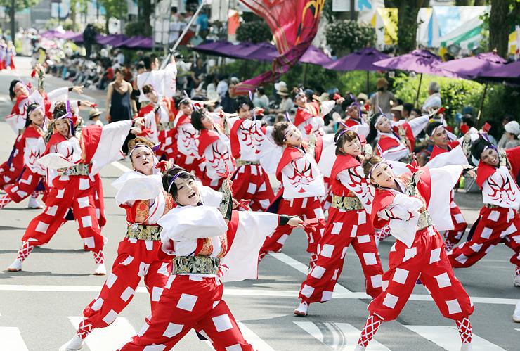 躍動感あふれる踊りを披露する参加者=富山市の城址大通り