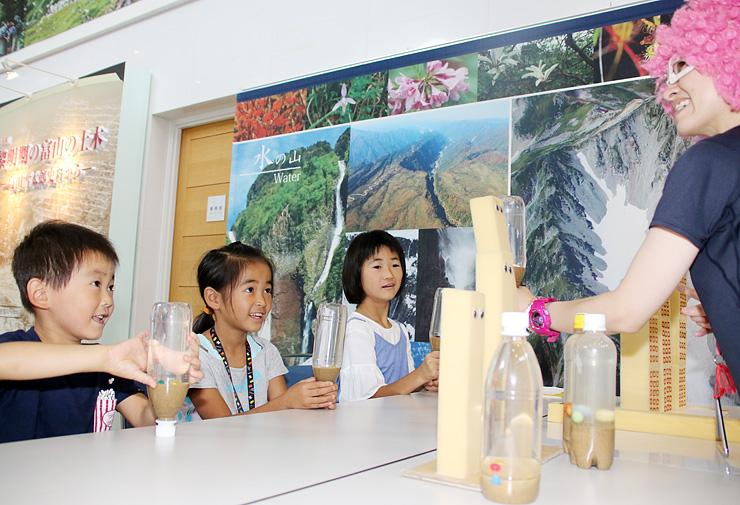 ナダレンコさん(右)からペットボトルを使って液状化現象を学ぶ子どもたち