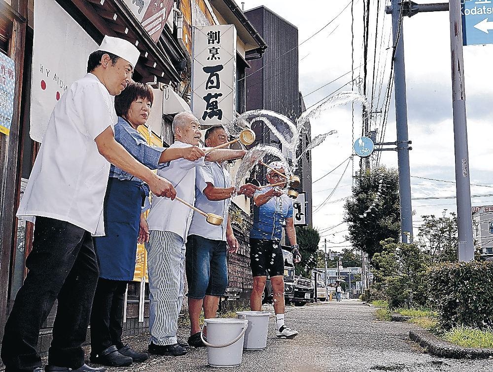 店先に水をまく飲食店関係者=金沢市笠舞3丁目