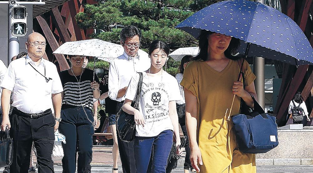 強い日差しの下、日傘を差して歩く人=JR金沢駅前