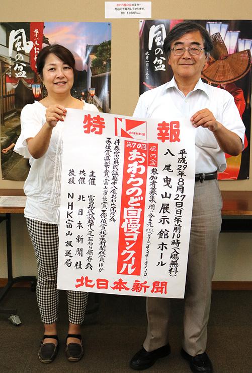 ポスターを手に笑顔を見せる保存会メンバー
