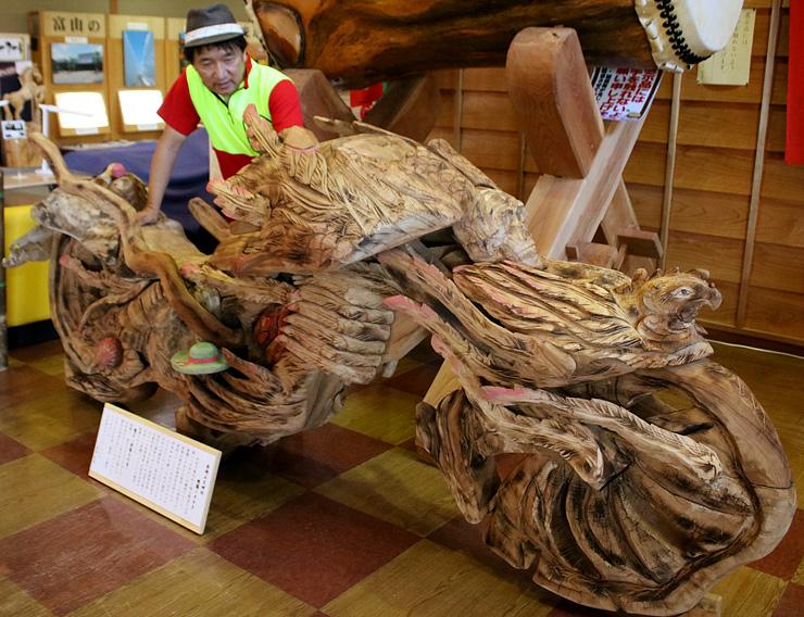 被爆クスノキで作ったオートバイを眺める音琴さん=いなみ木彫りの里創遊館