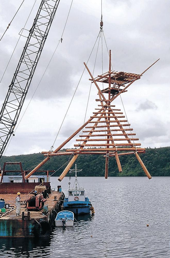 クレーンでつり上げられたボラ待ち櫓=穴水町比良の中居湾ふれあいパーク