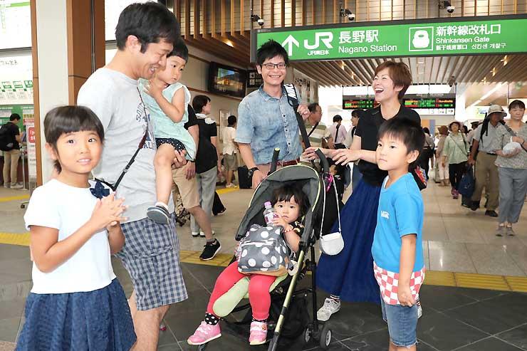 新幹線で帰省した親戚(右の4人)を笑顔で迎える親子連れ=11日午前11時3分、JR長野駅