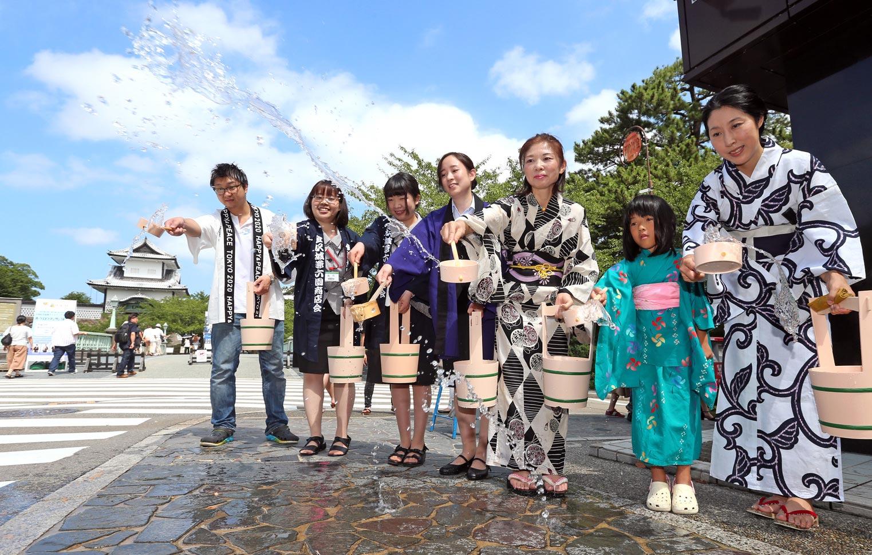ひしゃくで水をまくメンバー=金沢市兼六町の紺屋坂