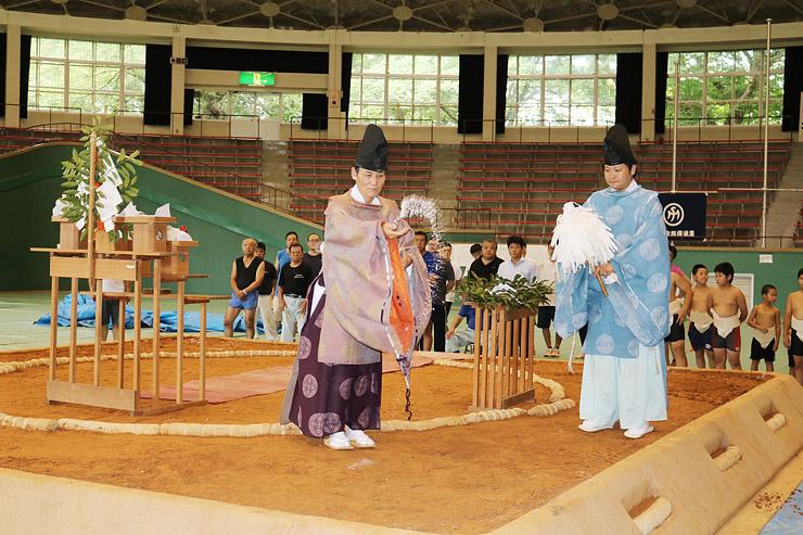 完成した土俵に塩をまく松本宮司(中央)=高岡市民体育館