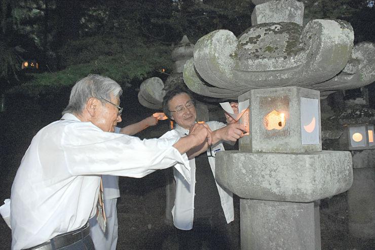 高島藩主諏訪家墓所の石灯籠に火をともす「史跡御廟保存会」の会員