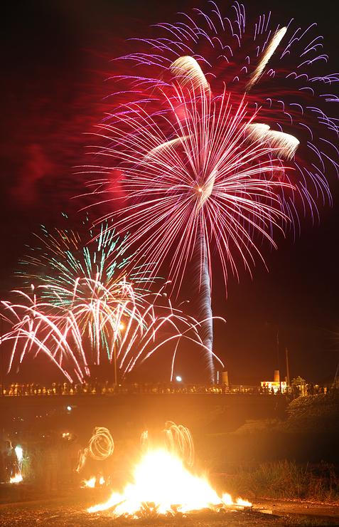 夜空を彩る大輪の花火とにおとんぼの炎=上市川の白竜橋上流