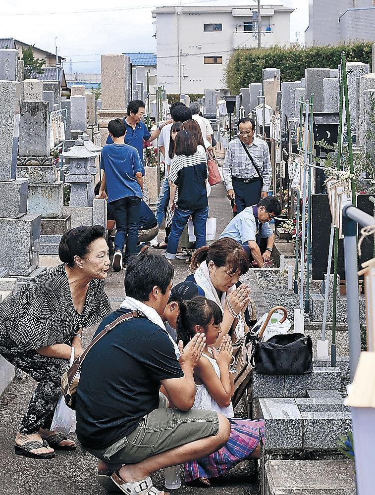 墓の前で手を合わせる家族連れ=白山市の松任中央墓地公苑