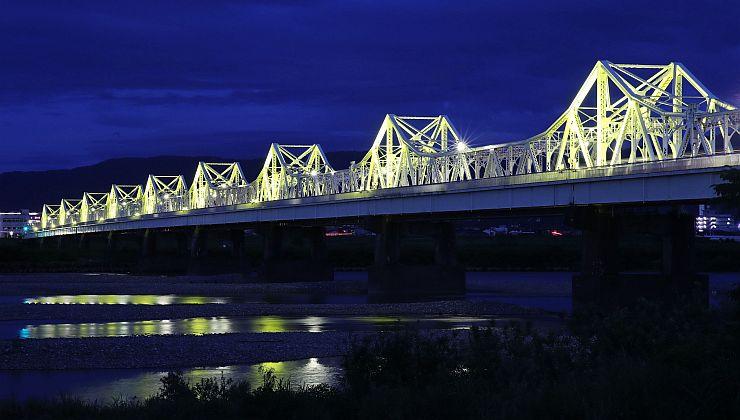 黄色の光でライトアップされ、夜空に浮かび上がった長生橋=14日、長岡市