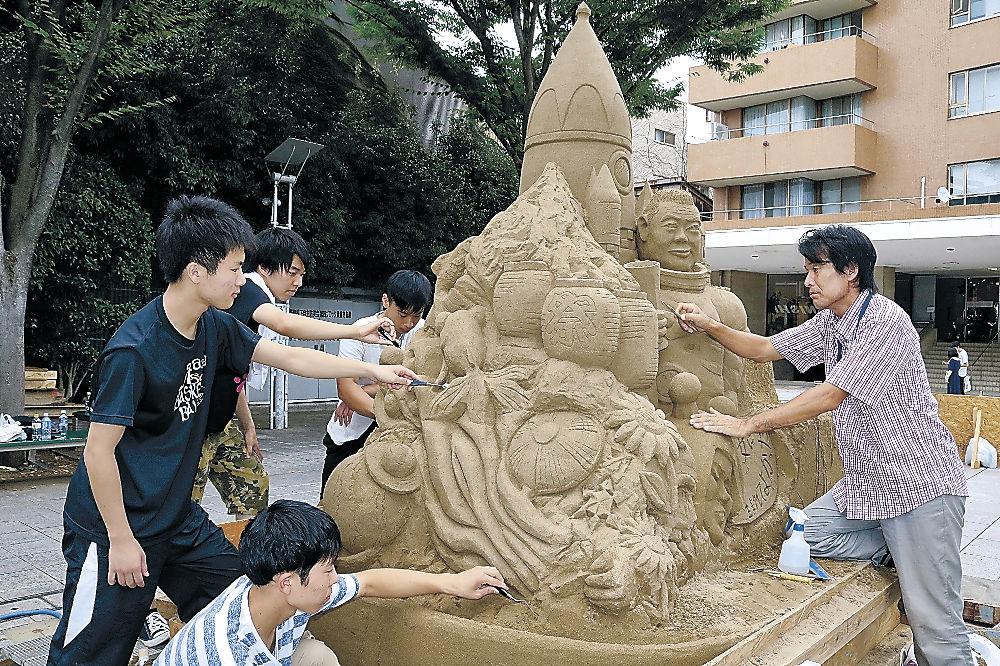 砂像作りに励む古永さん(右)と高校生=金沢市の竪町広場