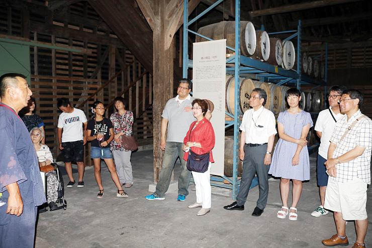 たるが並ぶウイスキー蒸留所で、担当者(左)の説明を聞く見学客=砺波市三郎丸