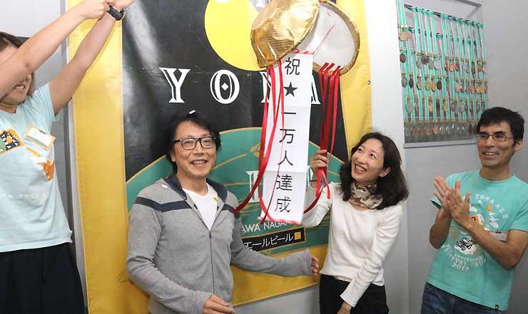 醸造所見学客1万人目となった石田さん(左から2人目)